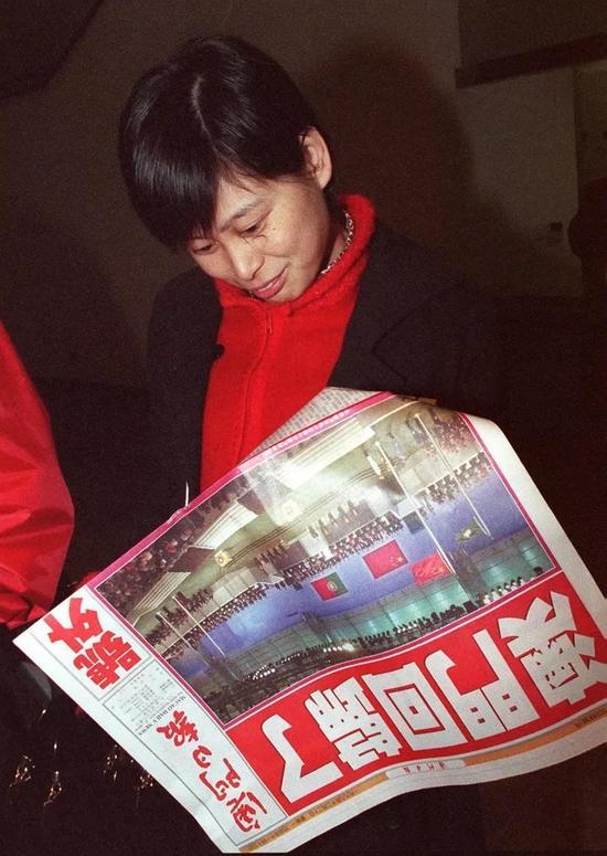 """1999年12月20日凌晨1时许,《澳门日报》出了第一份回归报道号外,头版大标题""""澳门回归了""""赫然醒目。这是一位市民在阅读该报号外。新华社记者 刘建国 摄"""