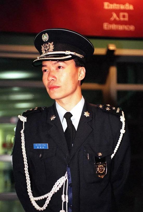 1999年12月20日是澳门回归祖国的第一天。从当天零时起,澳门警察全部佩戴上带有澳门特别行政区区徽图案的新警徽和新帽徽,取代了原先带有葡萄牙色彩的旧警徽。这是佩戴新警徽的警察在街头巡逻。新华社记者 鱼澜 摄