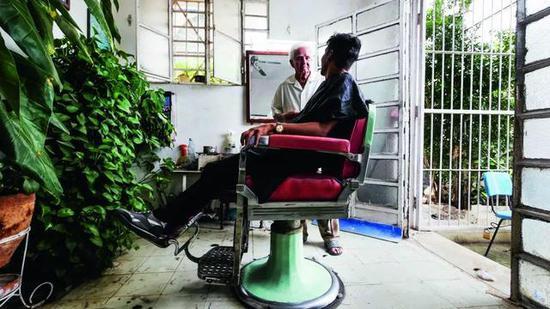 客户正等待91 岁的理发师为他修剪头发