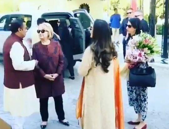 穆克什和妻子妮塔与克林顿交谈时,阿贝丁拿着花站在一旁。