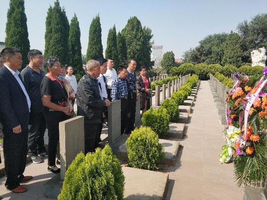 丁效飛烈士親人在墓前祭拜。