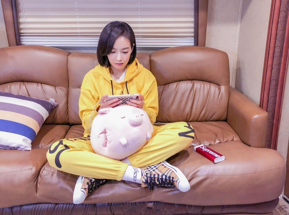 免费性爱黄色小�_宋茜短发俏皮可爱 一袭嫩黄运动装清新随性 躺沙发玩手机好嗨皮