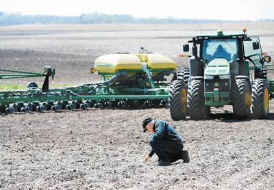 日前,在美国艾奥瓦州卡斯县大西洋镇,农场主比尔·佩雷特在检查播下的种子是否合乎耕作要求。对眼下的美国农民来说,最大的祈愿便是中美贸易能早日跨过寒冬。王 迎摄(新华社发)
