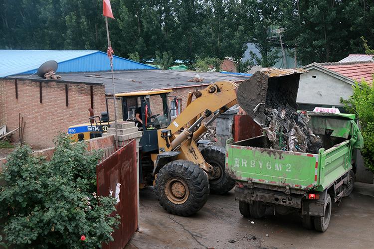 现场执法人。员对。厂区大门处的垃圾堆进走处理。
