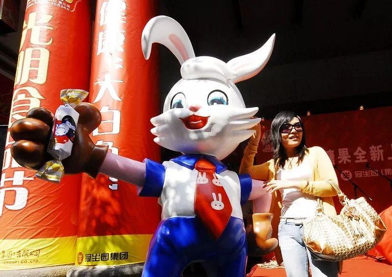 ▲别名上海市民在南京路上海第一食品商店门口和刚摆放的大白兔奶糖卡通现象相符影。(新华社)
