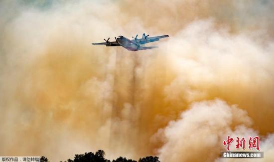 资料图:当地时间2019年6月9日,美国加州,北加州山火持续蔓延,危险急剧升高,天然气和电力公司对部分地区约1700名客户进行停电措施。图为当地出动飞机进行灭火降温作业。
