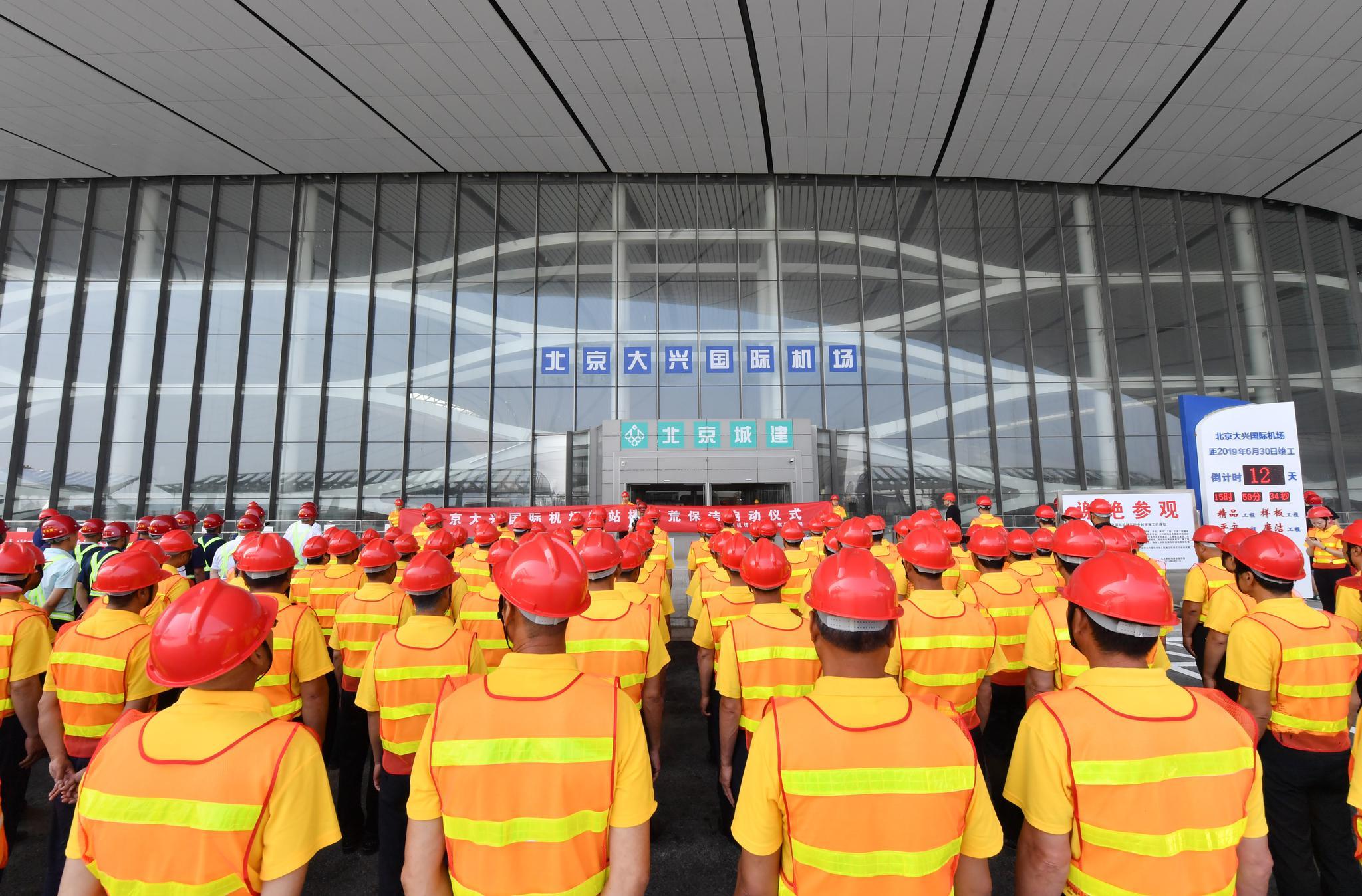 保洁人员在倒计时牌前集结就位。摄影/新京报记者李木易