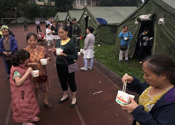6月18日,在長寧縣雙河鎮中學操場,群眾吃上熱粥。新華社 圖
