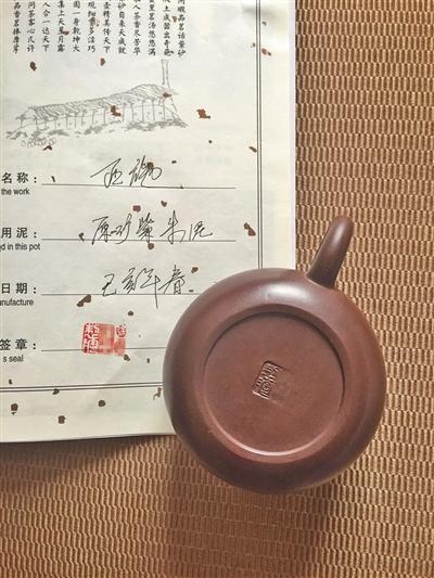 6月22日,在宜兴中国陶都陶瓷城买到的刻有国家工艺美术师徐某名字的紫砂壶,商家现场模仿签名售卖。