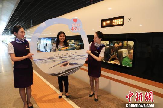 上海虹桥站开站以来的第4亿名旅客沈子怡在复兴号列车前合影留念。 殷立勤 摄