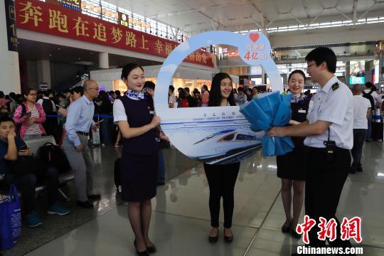 上海虹桥站开站以来的第4亿名旅客沈子怡接过工作人员送上的礼物。 殷立勤 摄