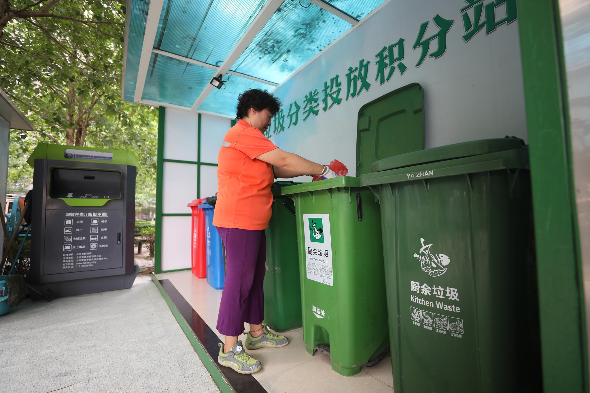 昨日,石景山区八宝山街道远洋沁山水南社区,工作人员将垃圾投入对应的垃圾桶中。 新京报记者 王飞 摄