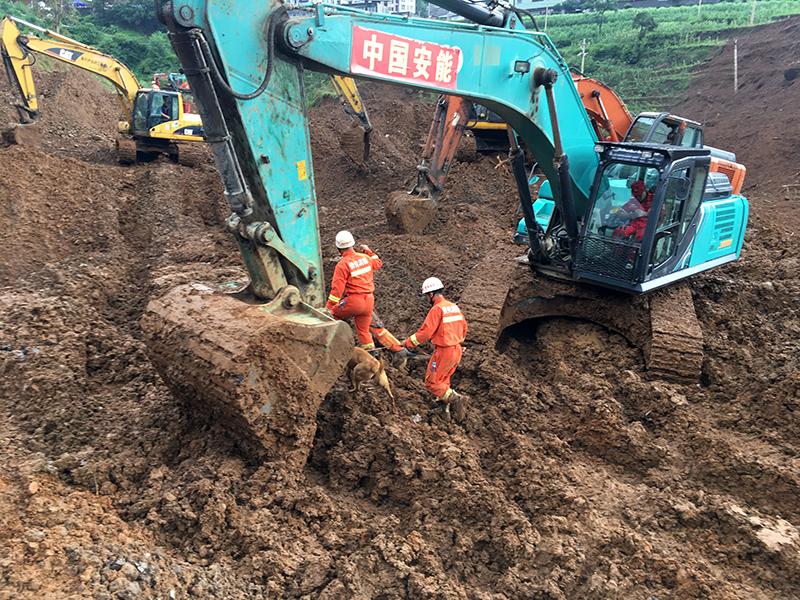 救援人員在山體滑坡現場操作工程機械開展救援。