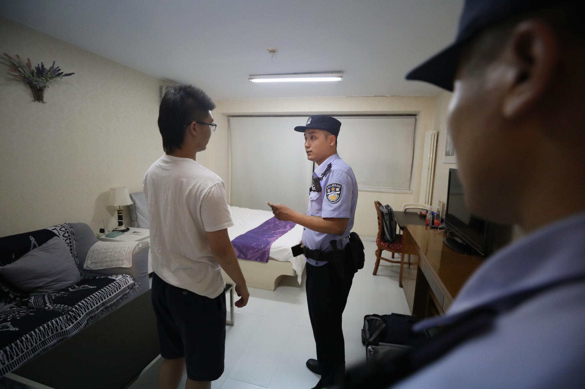 民警对住户进行询伟拿磐崴梗新京报记者王飞摄