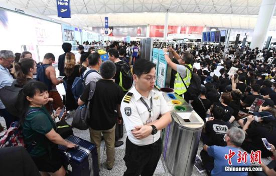 8月12日下午三时许,大批非法集结于香港国际机场的示威者拆走铁马,进入原先只限持机票旅客才可进入的离境大堂禁区前通道位置。受非法集结影响,大批登机旅客受阻,航班取消。 中新社发