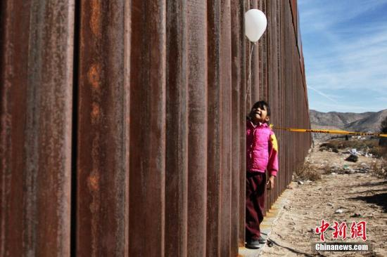 材料图:一名孩子在美墨边疆 墙旁。