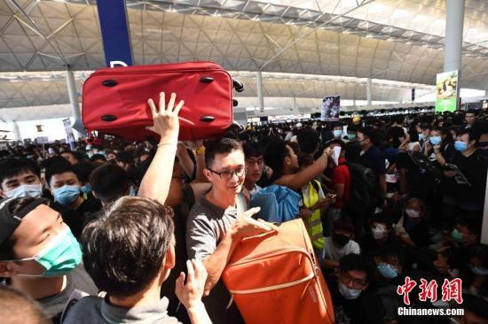 8月12日下午三时许,大批非法集结于香港国际机场的示威者拆走铁马,进入原先只限持机票旅客才可进入的离境大堂禁区前通道位置。受非法集结影响,大批登机旅客受阻,航班取消。中新社记者 麥尚旻 摄