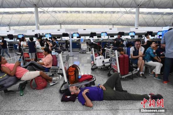8月13日下午,大批示威者以机场手推车等堵塞香港国际机场1号客运大楼旅客登机行段及保安闸门,旅客未能经1号客运大楼前往离境大堂。 中新社记者 麦尚旻 摄
