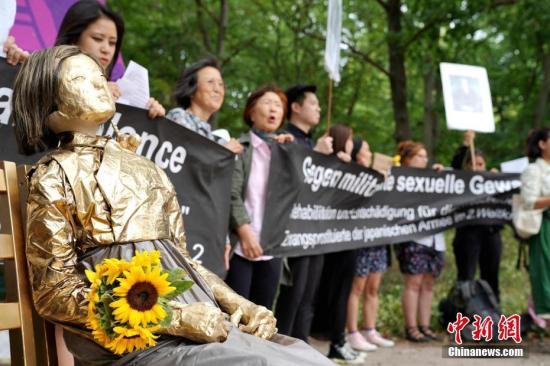 """资料图:2018年8月14日,旅德的韩国和日本民间团体在柏林举行集会,要求日本政府向""""慰安妇""""制度暴行受害者正式道歉,并作出赔偿。中新社记者 彭大伟 摄"""