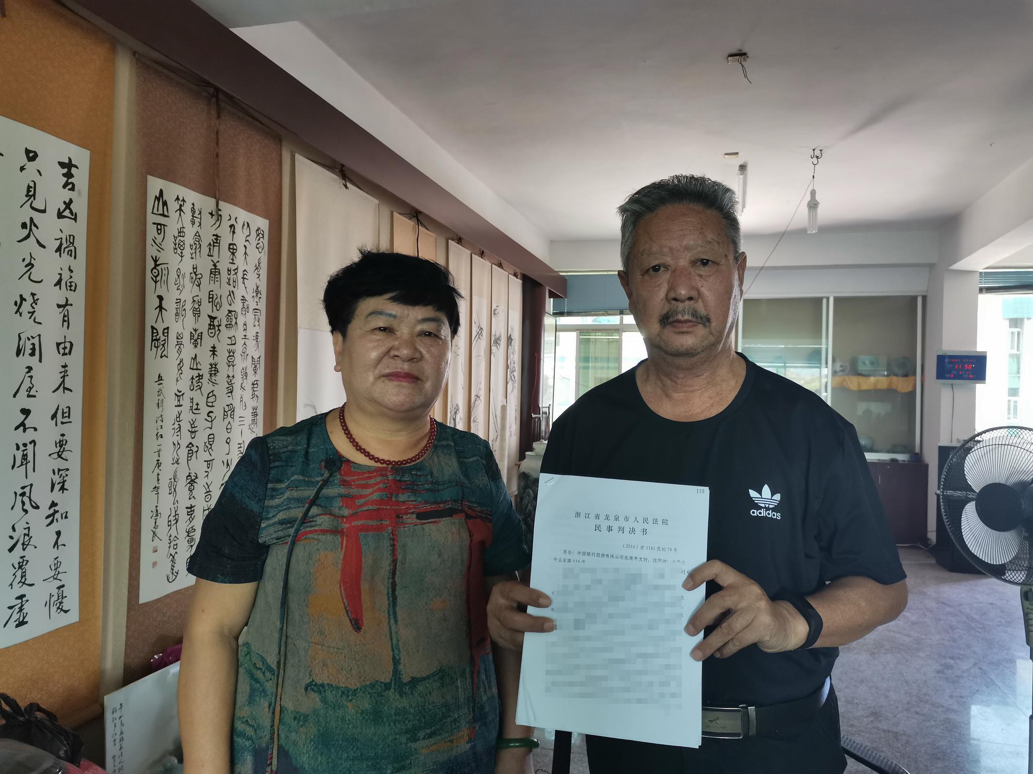 2019年7月17日,李成恩、蔡仁英在家中向新京报记者展示判决书,他们所在的房子已被抵押。 新京报记者 韩茹雪 摄