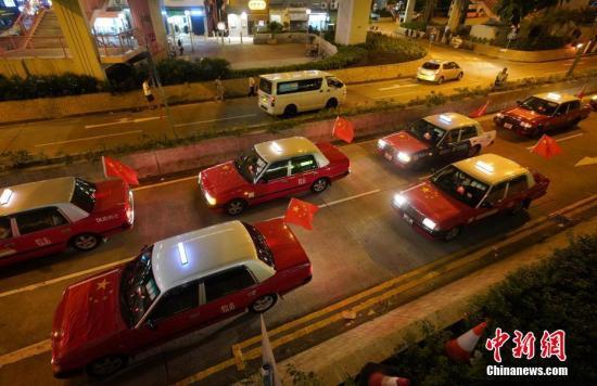 """资料图:8月23日晚,""""守护香港大联盟""""联同香港的士司机从业员总会发起""""守护香港·风雨同舟""""大行动,在港岛筲箕湾中心,有超过140多辆出租车车身贴着海报,车尾悬挂五星红旗依次有序驶向主干道,呼吁社会反对暴力。中新社记者 张炜 摄"""