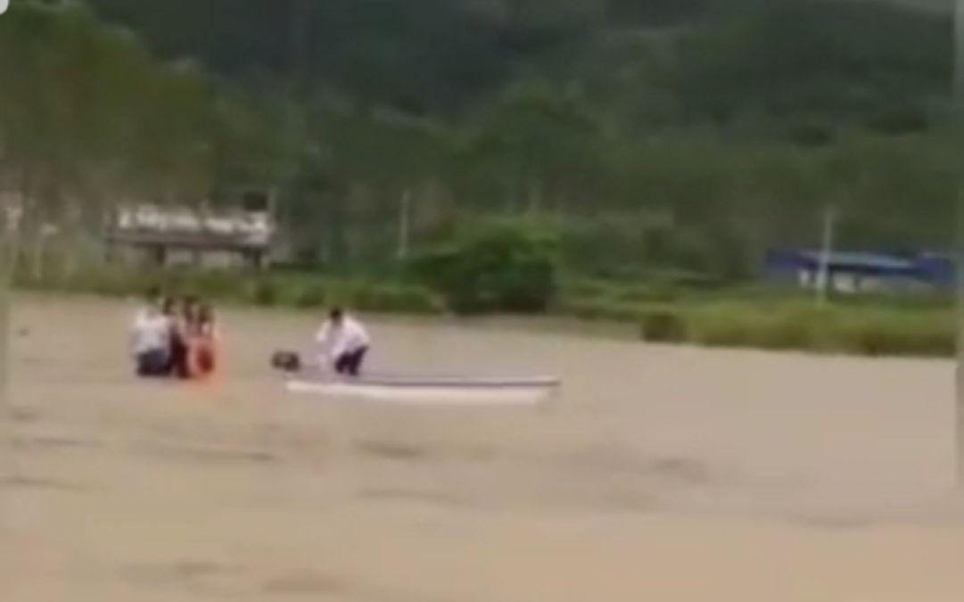 一处道路附近,多人在水中站立,脚下车辆已被十足占有。一艘冲锋艇驶向被困人员进走拯救。视频截图