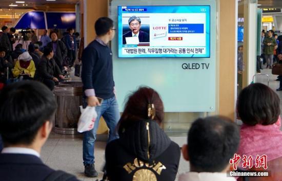 资料图:当地时间2018年4月6日,韩国首尔火车站,人们观看韩国前总统朴槿惠案一审宣判的直播画面。中新社记者 吴旭 摄