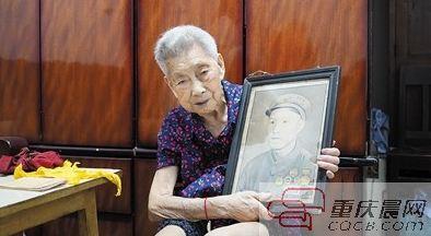 余婆婆手持老伴的遗像。