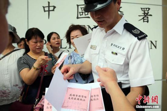 """8月10日,""""守护香港大联盟""""当天在香港各区发起""""全民撑警日""""活动。资料图为市民将慰问卡及签发递交中区警署值日警官。中新社记者 洪少葵 摄"""