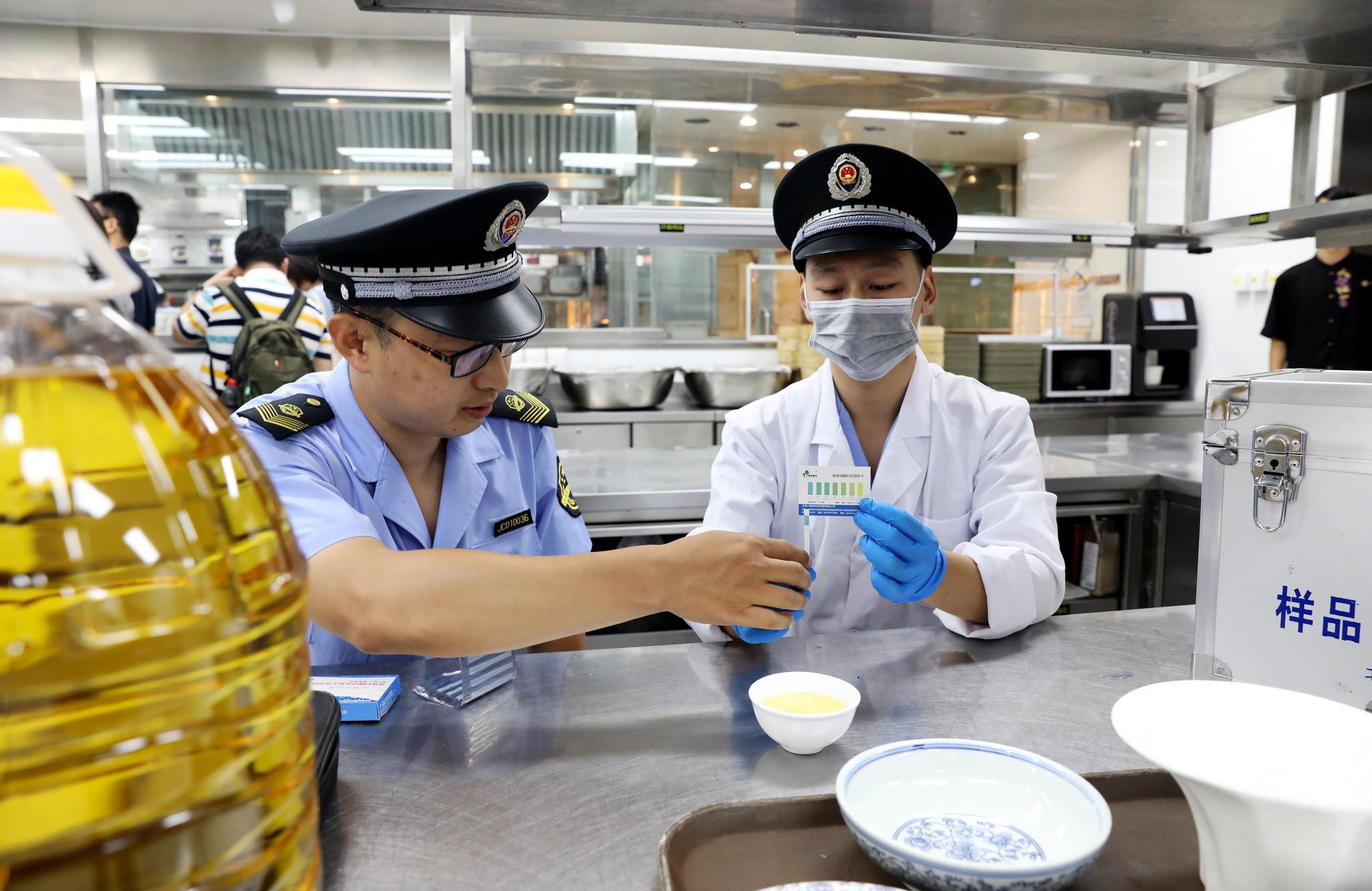 执法人员对餐厅使用的食用油进行现场检测。摄/通讯员 何筱强