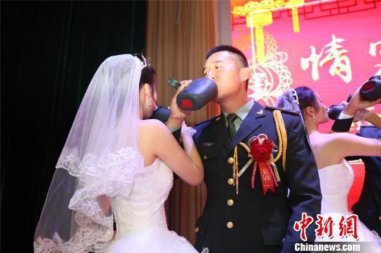 """新人们用军用水壶喝""""交杯酒"""" 贾方文 摄"""