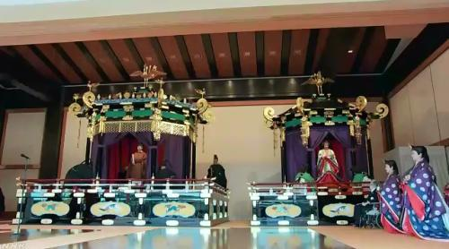 """日本德仁天皇身着传统装束""""黄栌染御袍""""站在""""高御座""""上,宣告即位。(图片来源:NHK视频截图)"""
