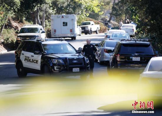 当地时间10月31日深夜,美国北加州奥林达一个万圣节派对上发生枪击事件,造成5人死亡,多人受伤。图为11月1日,一名警员在案发地附近与同事交谈。中新社记者 刘关关 摄