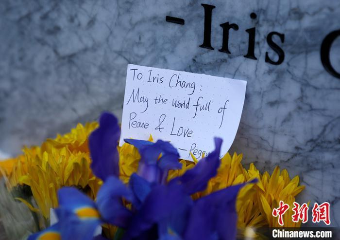 图为人们向刻有张纯如生平简介注册新宝GG纪念碑献花。中新社记者 刘关关 摄