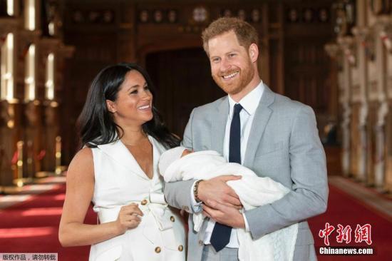 资料图:英国哈里王子和梅根夫妇抱着刚出生的儿子在温莎城堡的圣乔治大厅合影。
