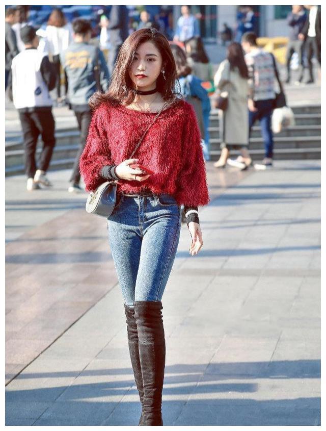 美女的红色上衣搭配牛仔裤,加上长靴,自信的搭配更时尚