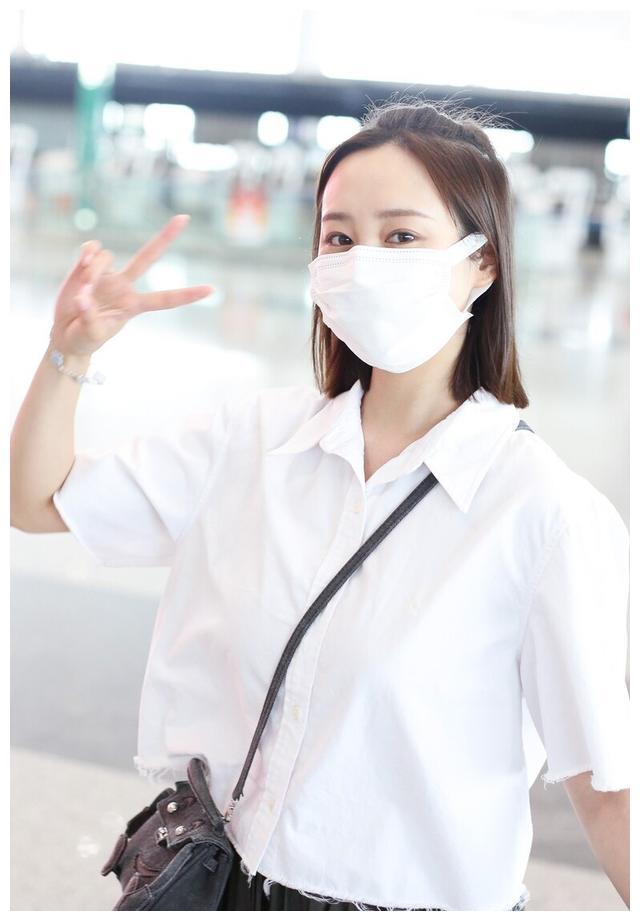 李纯身穿白色短T搭配半身裙现身机场休闲舒适面对镜头开心比耶
