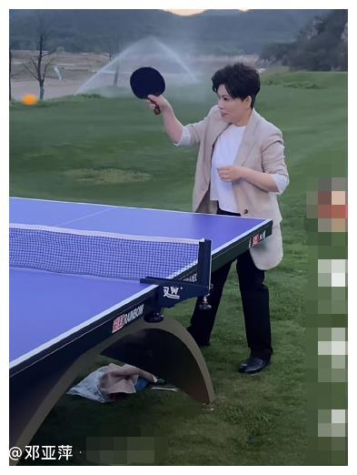 邓亚萍站大风中打乒乓球,身材娇小动作矫健,脚下杂物随地乱放