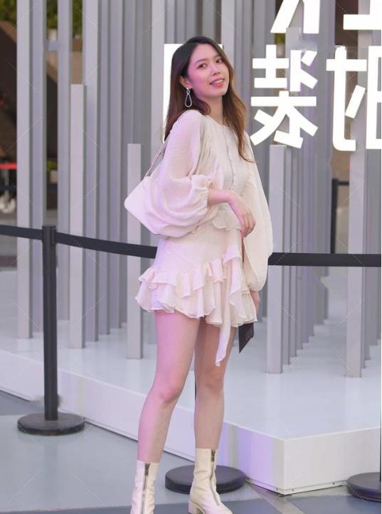 粉色花边连衣裙搭配皮靴,泡泡袖的设计仙气十足,尽显青春的气息