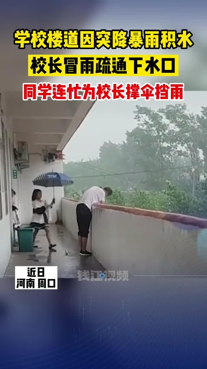 河南一学校校长冒雨清理下水口,学生为他撑伞挡雨