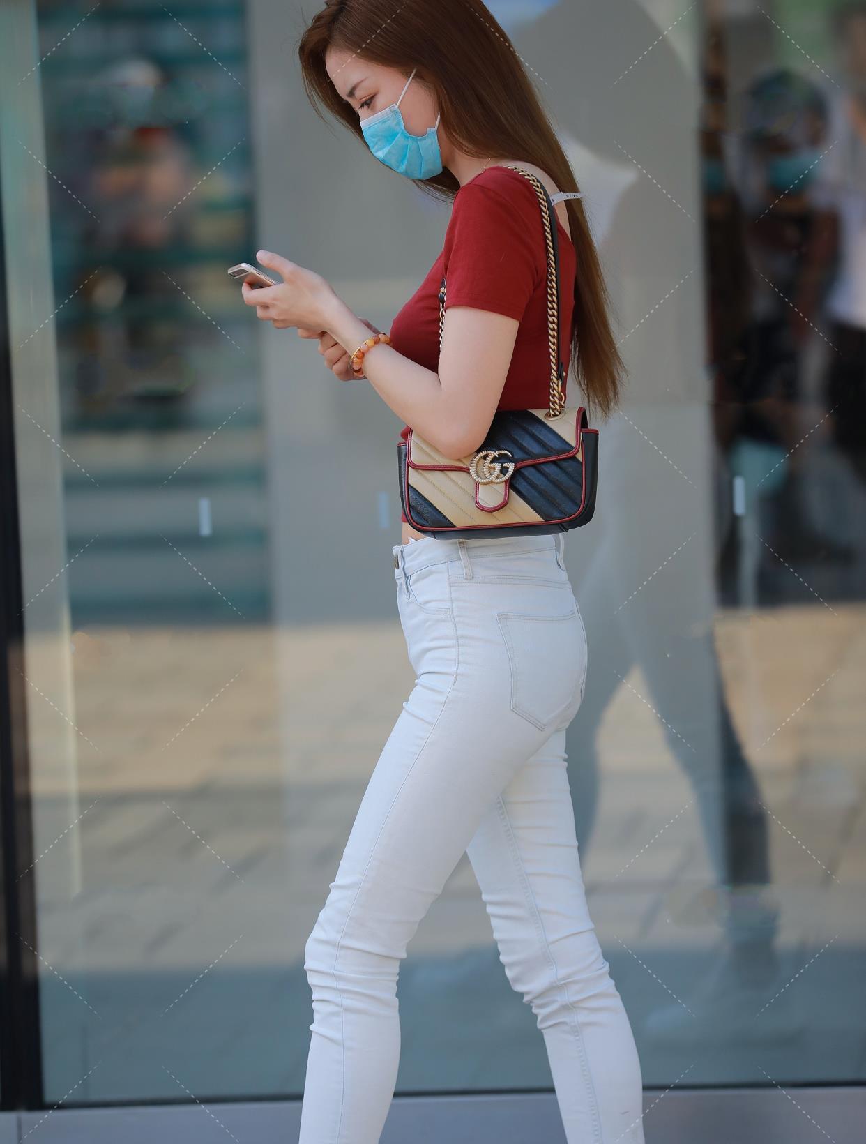 红色V领修身T恤搭配浅色牛仔裤,适合身材高挑的女性
