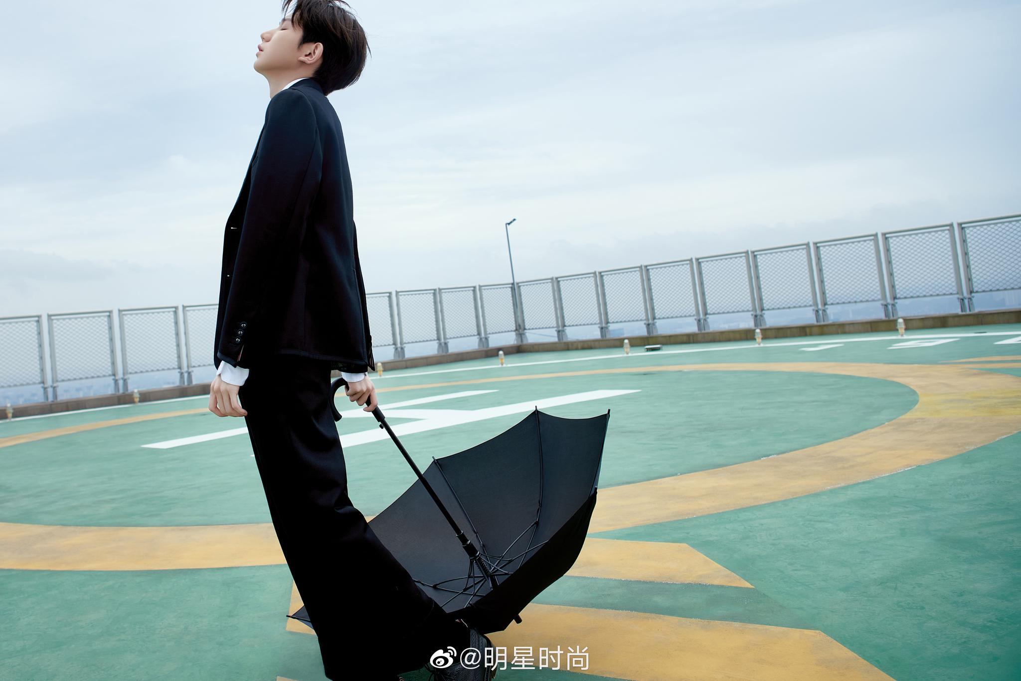 一身正装的小哥哥手持雨伞和鲜花……