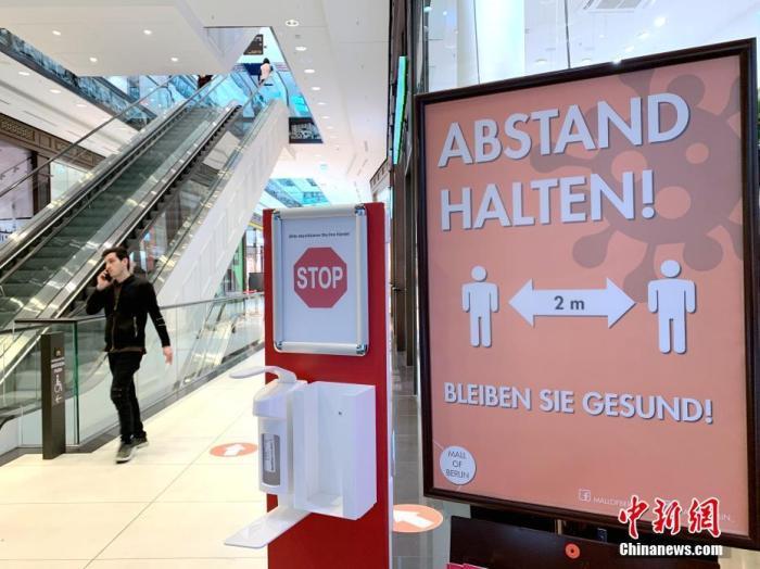 当地时间4月30日下午,柏林市中心一家日前已重新开放的购物中心在门口放置了手部消毒液,并提醒人们保持两米距离。 中新社记者 彭大伟 摄