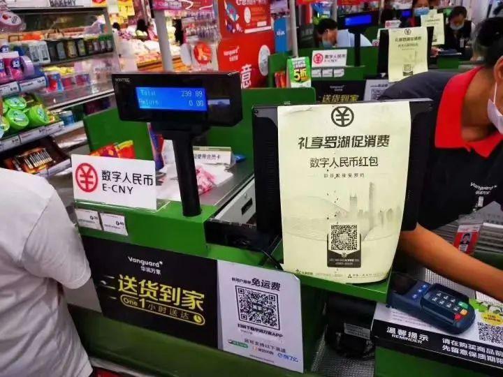 图为在深圳华润万家罗湖区春风店,人工收银台有标识提示顾客可使用数字人民币。