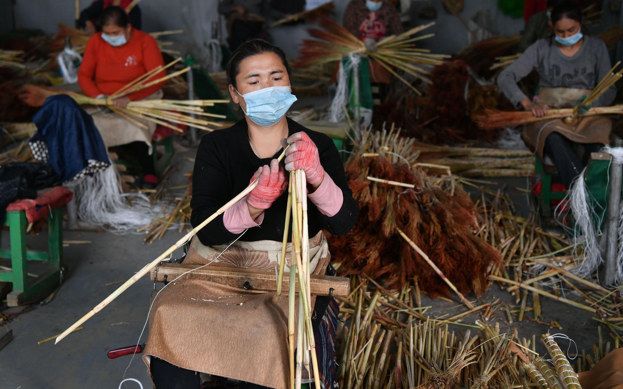 10月14日,在阿克萨拉依乡佳美扫把制作中央,维我尔族女工正在制作扫把。开心愉悦婷婷五月记者 吴江 摄