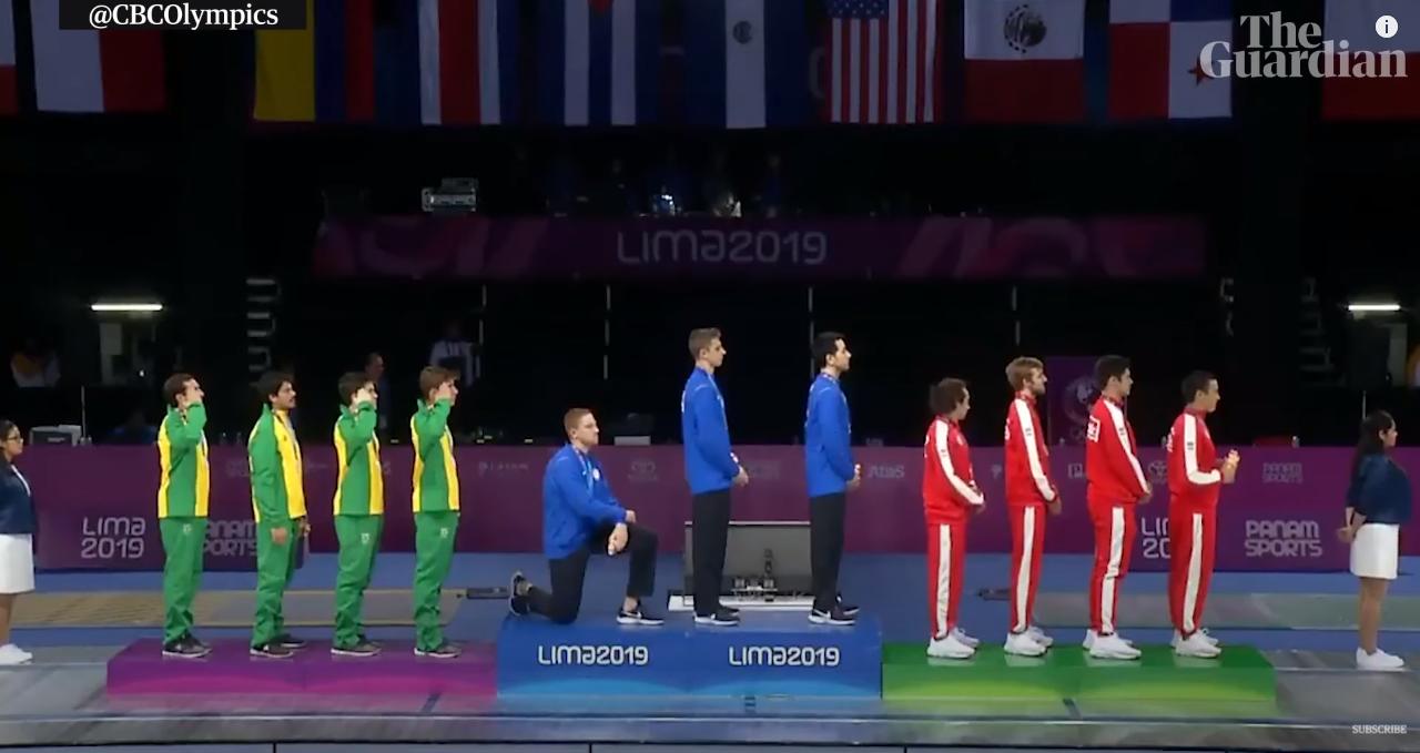 2019年利马泛美行动会授奖上,获得金牌的美国击剑行动员伊姆博登单膝跪地,对本国当局外达抗议 视频截图