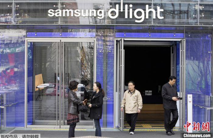 原料图:韩国首尔,人们站在三星电子总部的展现厅外。