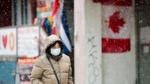 今年2月终,走人戴着口罩冒雪走走在添拿大多伦多商业区。(原料图片)