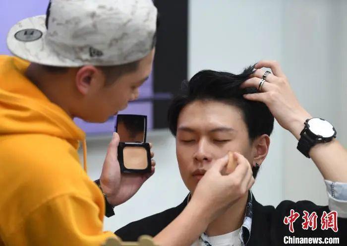 原料图:男性化妆师在为男模特化妆。