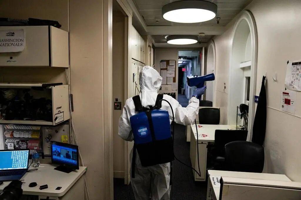 本周,包括简报室在内的白宫部分地区就像是一个危险区域。身着全套防护服的工作人员在对公共场所进行消毒。图源:《纽约时报》